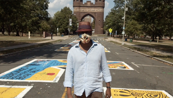A Black man wearing a mask and walking down a street covered in murals.