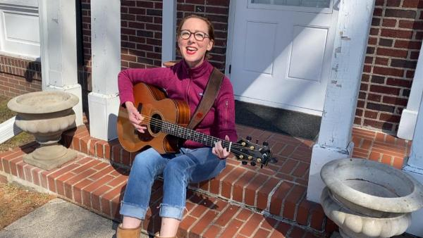 A musician sitting on a porch with a guitar across their lap.