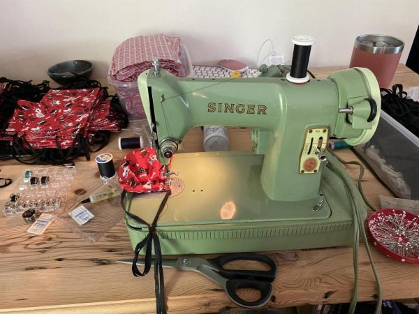 An old, green Singer sewing machine being used to make masks.