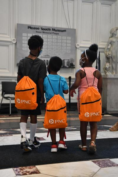 Three young Black children with backpacks from Summer Discovery Backpacks