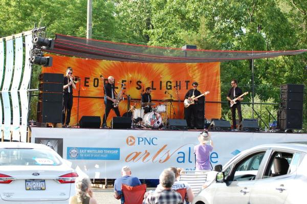 "A band on stage with guitars, brass and drums and an orange tie-dye banner that reads ""Peoples Light"" behind them."